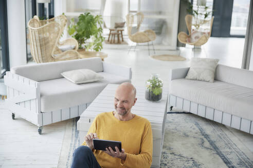 Mature man using digital tablet while sitting on floor at home - FMKF06812