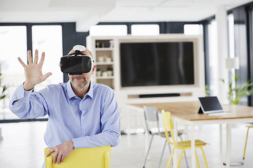 Businessman wearing virtual reality headset touching while sitting on chair - FMKF06824