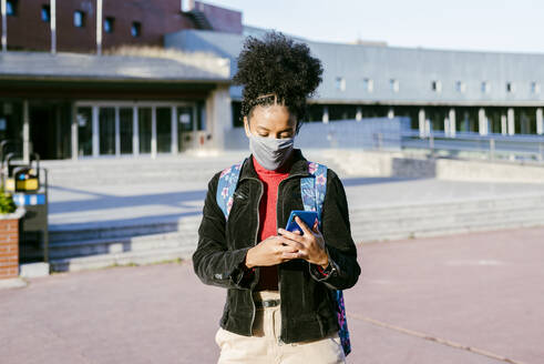 Student wearing protective face mask using smart phone while standing at city street - MARF00001