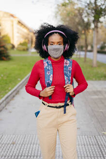 Woman wearing protective face mask and headphones carrying backpack while standing on footpath - MARF00007