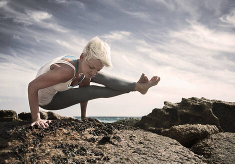Blond woman practicing Astavakrasana on rock formation at beach against sky - AJOF00889