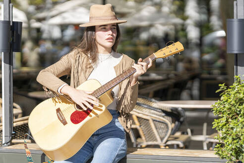 Young woman playing guitar while sitting on bench during sunny day - GGGF00255