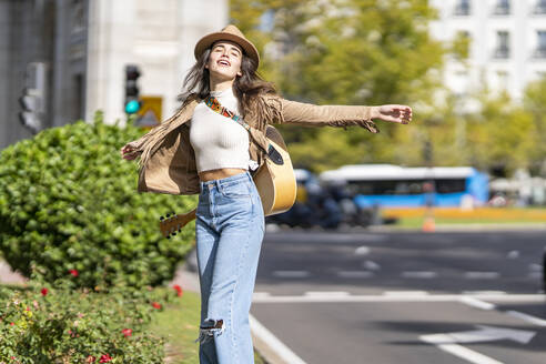 Carefree woman with arms outstretched standing on street in city - GGGF00273