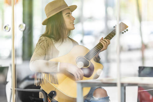 Smiling young female musician playing guitar seen through glass at cafe - GGGF00288