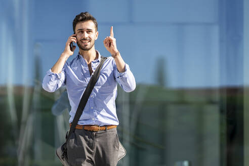 Businessman wearing crossbody bag pointing upward while talking on mobile phone outdoors - GGGF00372