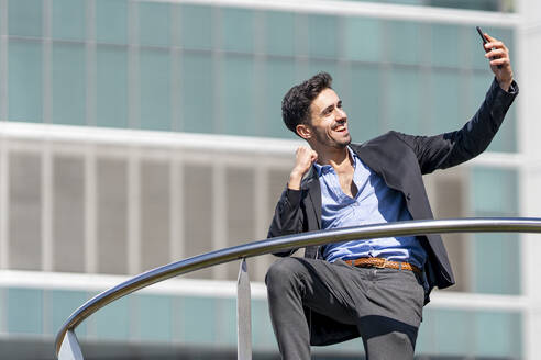 Smiling businessman cheering while taking selfie through mobile phone standing outdoors - GGGF00375