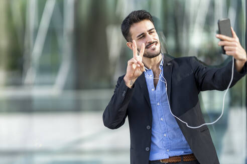 Confident businessman showing peace sign while taking selfie - GGGF00378