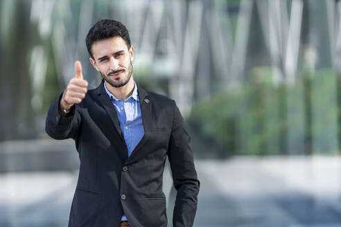 Young businessman wearing suit showing thumbs up while standing outdoors - GGGF00381
