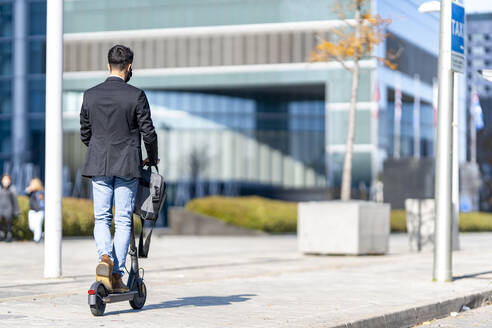 Businessman riding push scooter on footpath - GGGF00384