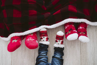 Parents and baby boy wearing Christmas socks at home during Christmas - EBBF01693
