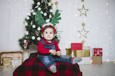 Baby boy wearing horned headband sitting against Christmas tree at home during Christmas - EBBF01696