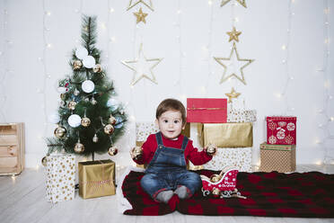 Cute boy playing with bauble while sitting on blanket at home during Christmas - EBBF01699