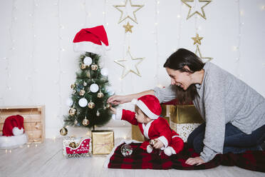 Mother and son playing with bauble on Christmas Tree while sitting on blanket at home - EBBF01702