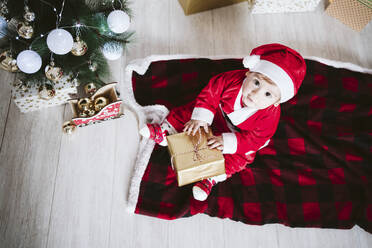 Baby boy in Santa Claus costume playing with gift box while sitting at home during Christmas - EBBF01705