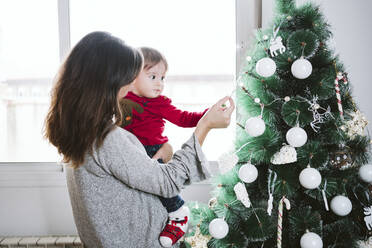 Mother showing decoration to baby boy while standing at home during Christmas - EBBF01708