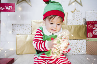 Baby boy in elf costume playing with illuminated string lights in bottle while sitting at home during Christmas - EBBF01711