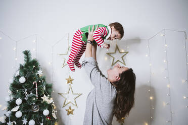 Smiling woman picking up baby boy while playing at home during Christmas - EBBF01714
