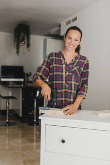 Smiling woman using electric drill on wood material while standing by cabinet at home - DMGF00388