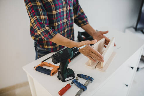 Woman working with wood and tool at home - DMGF00415