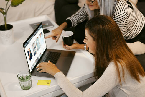 Women doing online shopping on laptop while sitting at home - ERRF04781