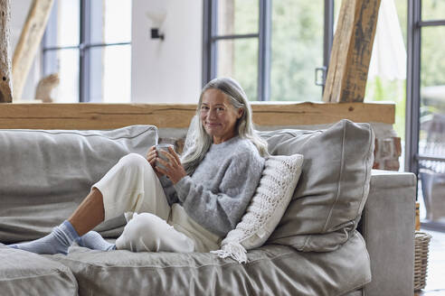 Smiling mature woman holding coffee cup while sitting on sofa at home - MCF01513