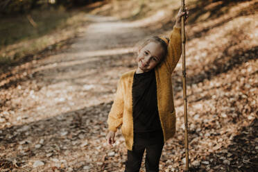 Girl smiling while holding stick standing on forest path - GMLF00889