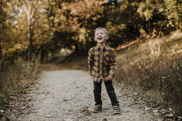 Cheerful boy looking away while standing on forest path - GMLF00892