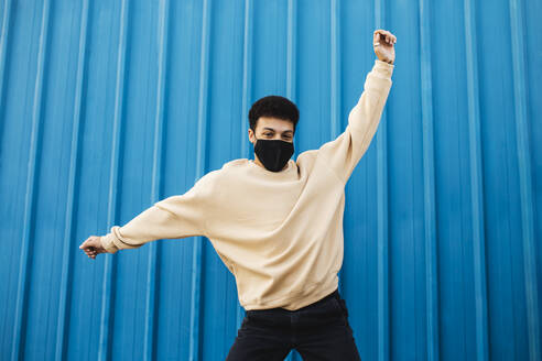 Young man wearing protective face mask dancing while standing against blue wall - MIMFF00282