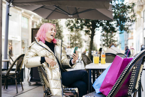 Pink hair woman using mobile phone while sitting with shopping bags at sidewalk cafe - MARF00024