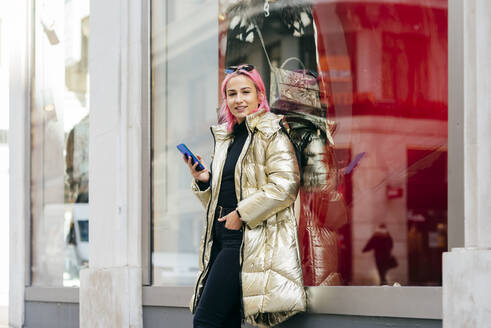 Fashionable woman using mobile phone while standing with hands in pockets against window - MARF00027