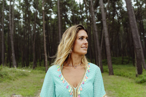 Beautiful woman looking away while standing at forest - MARF00029