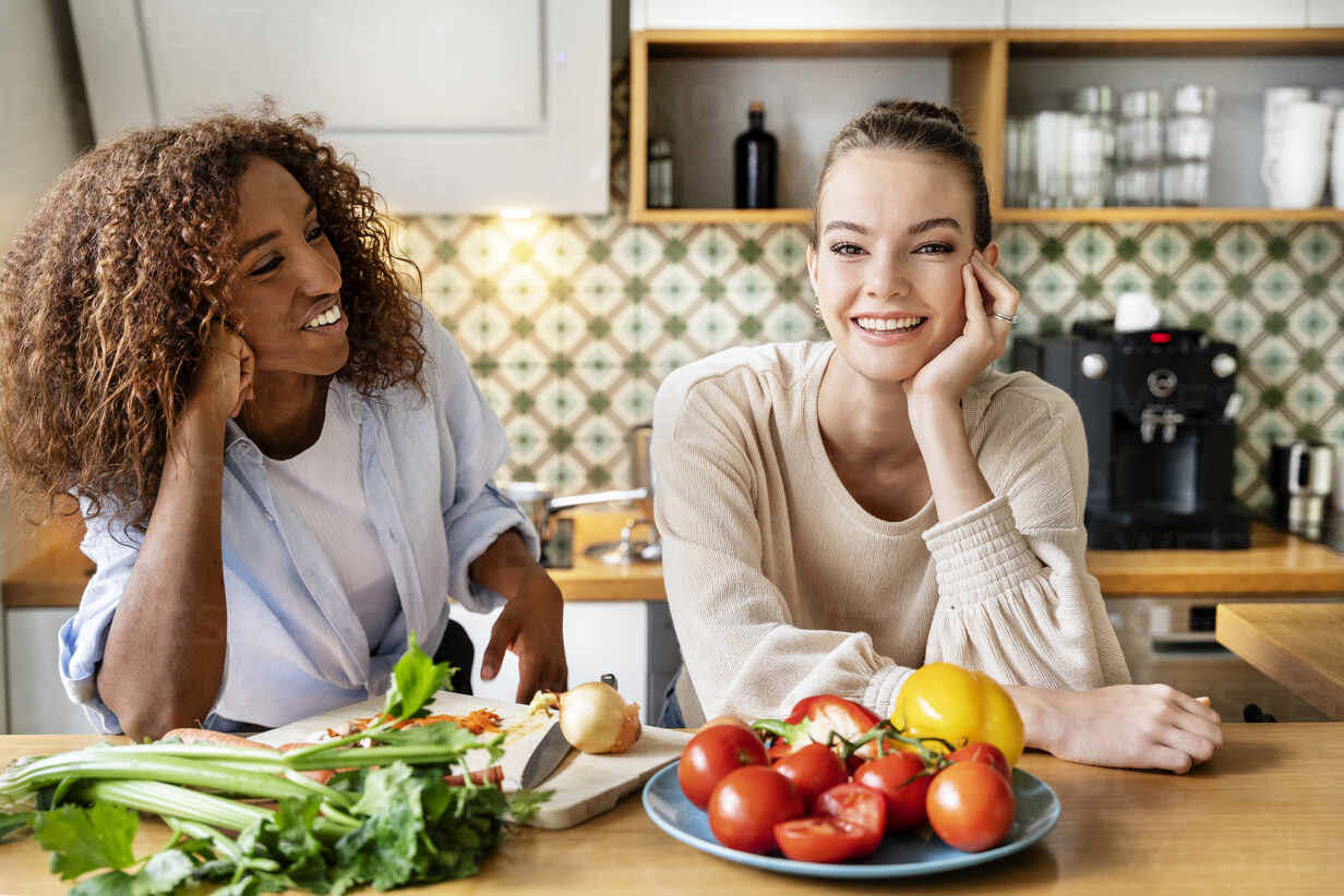 Female Colleagues With Hand On Chin Leaning On Counter In Office Kitchen Stockphoto