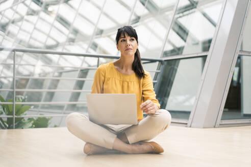 Businesswoman with laptop sitting on floor in office corridor - JOSEF02605