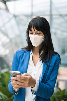 Female entrepreneur text messaging on mobile phone in office during pandemic - JOSEF02638