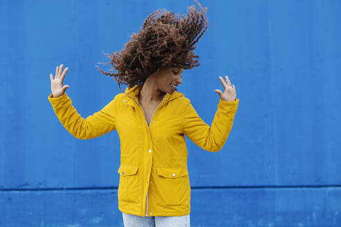 Playful woman tossing hair while standing against blue wall - JCZF00352