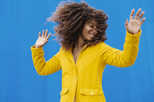 Smiling young woman in yellow jacket tossing hair while standing against blue wall - JCZF00355