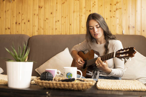 Young woman playing guitar while sitting at home - LJF01875