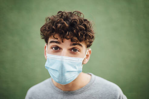 Young man with surgical mask against green background - MIMFF00312