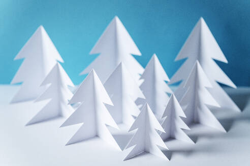 Paper forest with white trees on table against blue background - GEMF04455