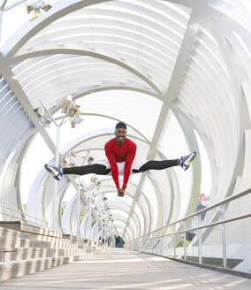 Acrobat jumping while doing the splits on walkway - JCCMF00149