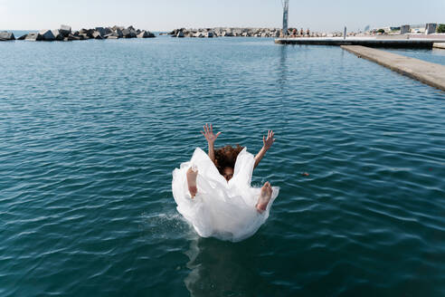 Unrecognizable young barefoot female in white wedding dress falling in rippling lake near pier looking at camera - ADSF19168
