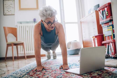 Woman following online yoga class - CUF56632