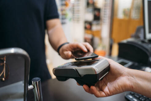 Mid adult man making contactless payment through mobile phone - MPPF01315