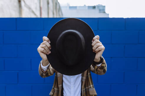 Stylish man wearing checked jacket holding black hat in front of face against blue wall - XLGF00891