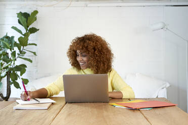 Happy businesswoman with laptop writing in notepad while working from home - VEGF03305