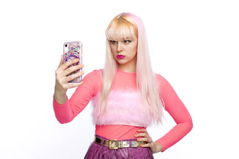 Fashionable young woman taking selfie on smart phone against white background - FLLF00547