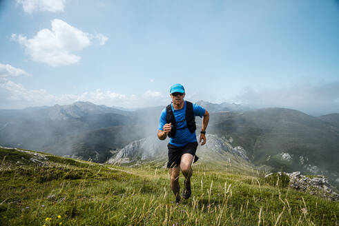 Mature sportsman trail running in the mountains on meadow against blue sky - JMPF00712