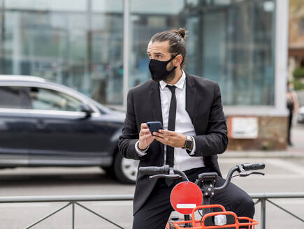 Portrait of businessman wearing protective face mask sitting on bicycle with smart phone in hands - JCCMF00202