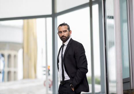 Portrait of bearded businessman standing indoors with hands in pockets - JCCMF00211