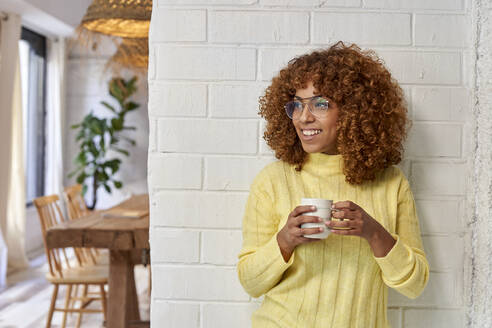 Woman looking away while having coffee against brick wall in cafe - VEGF03334